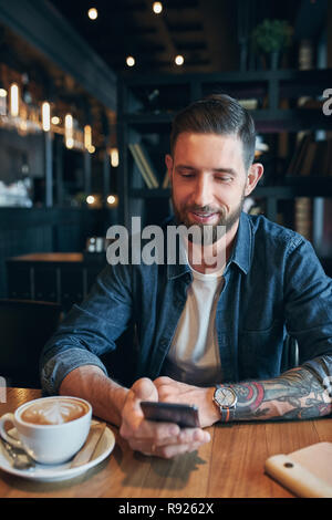 Young bearded businessman,dressed in a denim shirt, sitting at table in cafe and use smartphone. Man using gadget. - Stock Photo