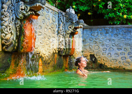 Young woman stand in thermal bath, relaxing under flowing water stream of shower in natural mineral hot spring Banjar. Day tour on family holidays. - Stock Photo