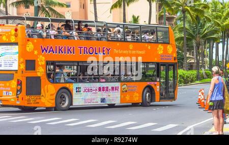 Waikiki, Hawaii - 25 May 2016: The  Waikiki Trolley bus shuttles visitors and local passengers throughout Waikiki, Honolulu and East Oahu on four sepa - Stock Photo