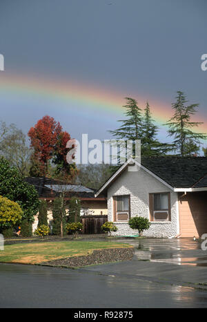 A beautiful rainbow appears over a suburban neighborhood in Northern California, USA - Stock Photo