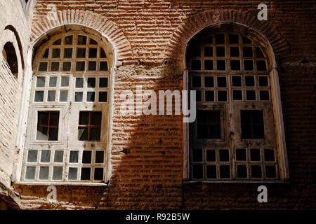Two windows in shade and light on tile brick wall - Stock Photo