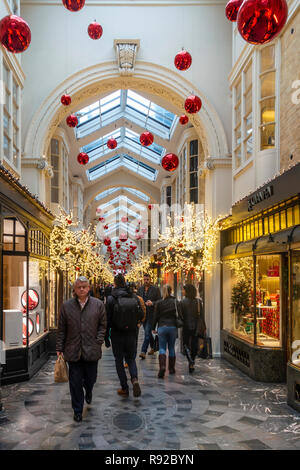 Shoppers walking through Burlington Arcade, a historic (1819) upmarket shopping arcade in Mayfair, central London, England, UK. The arcade is decorate - Stock Photo