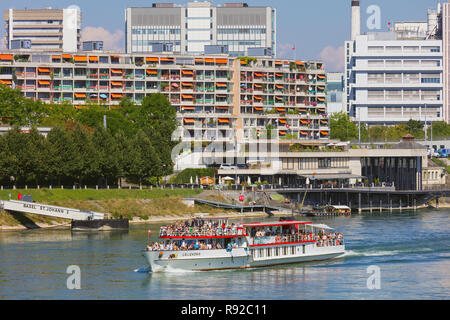 Buildings of  the city of Basel along the Rhine river, the Lallekonig boat with passengers on board passing - Stock Photo