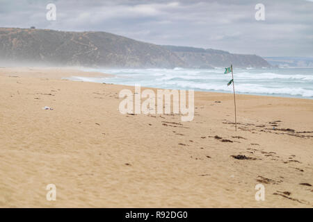 A flag over Tunquen Beach in Valparaiso region, an awesome and wild beach with a lot of wildlife because of it wetlands and turquoise waters - Stock Photo