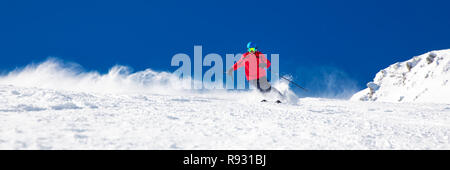 Man skiing on the prepared slope with fresh new powder snow. - Stock Photo