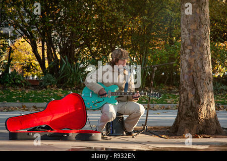 London, United Kingdom - November 18th, 2006: Unknown busker plays guitar and signs at Thames riverside. Street performers are performing often in thi - Stock Photo