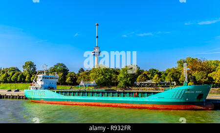 An ocean going freighter with the Euromast Tower in the background, seen from a tourist boat on the Nieuwe Maas River in the port of Rotterdam Holland - Stock Photo