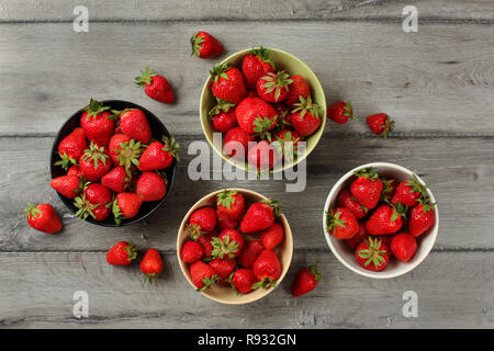Tabletop view - strawberries in small ceramic bowls, some of them spilled on gray wood desk. - Stock Photo