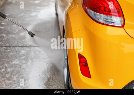 Rear wheel of yellow car washed with jet water in self serve carwash. View from behind. - Stock Photo