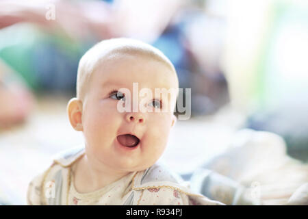 cute baby girl in fairy wings laughs while looking up at the camera. - Stock Photo