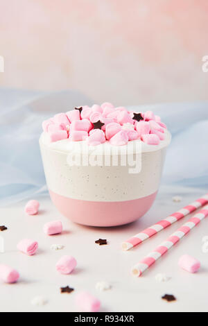 Hot chocolate or cocoa with whipped cream and pink marshmallow candy decorated with sugar snowflakes and chocolate stars in pink and white mug on whit - Stock Photo