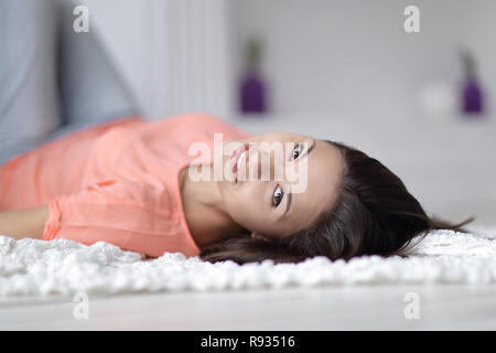 close up. young woman lying on white carpet in living room and looking at camera - Stock Photo