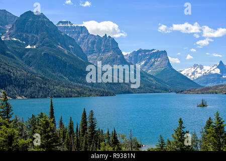 Wild Goose Island in Glacier National Park with Mountain Peaks in the Background - Stock Photo