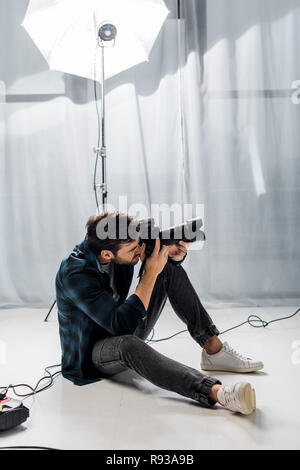 handsome young photographer with professional camera taking pictures in studio - Stock Photo