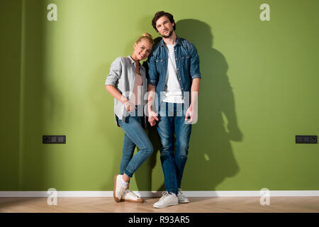 smiling couple holding hands, standing by green wall and looking at camera - Stock Photo