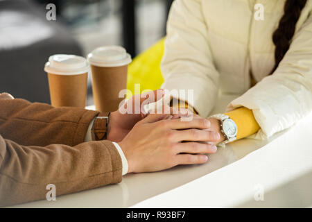 cropped view of loving couple holding hands at table with two disposable cups - Stock Photo