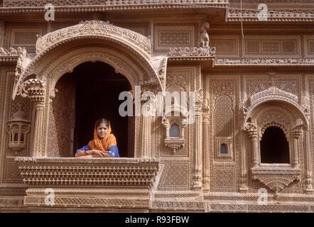 woman standing in Zarokhas windows balconies, Patwon ki Haveli, Jaisalmer, Rajasthan, India - Stock Photo