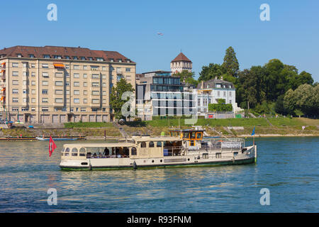 Buildings of the city of Basel, the Froschkonig boat with passengers on board passing along the Rhine river - Stock Photo