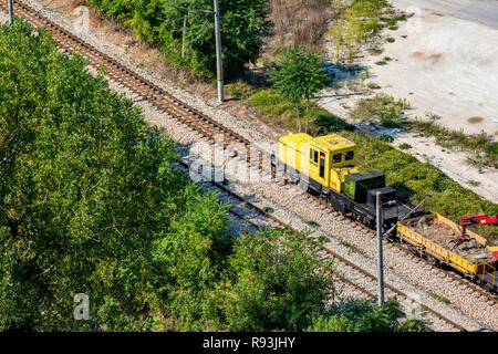 Yellow railway service diesel engine moving on rail line dragging wagons with pebbles and small red crane going to construction site. Rural Bulgarian  - Stock Photo