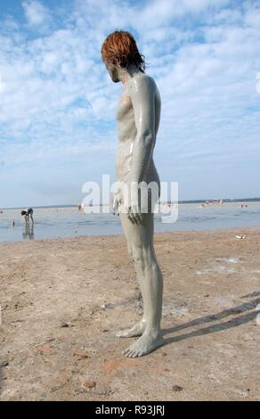 Man with a mud-covered body, at the Kuyalnik mud health spa, Kuyalnik Estuary, Odessa, Odessa Oblast, Ukraine - Stock Photo