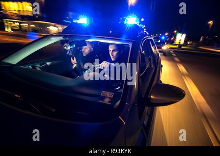 Police patrol car in an emergency operation, with blue lights and sirens - Stock Photo