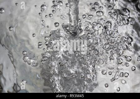 Water flowing into a basin, symbolic image for water consumption, wasting water - Stock Photo