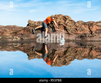 A Plogger/jogger collects plastic rubbish from beach during his morning run - Stock Photo