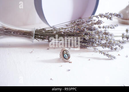 Vintage magical fantasy silver ring with lavander in the background. Magical colorful ancient stone - Stock Photo