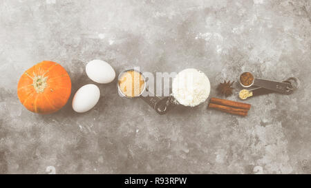 Ingredients for pumpkin pie - flour, pumpkins, eggs, cane sugar, various spices (nutmeg, ginger, cinnamon, anise) on a gray background. Top view. Food - Stock Photo