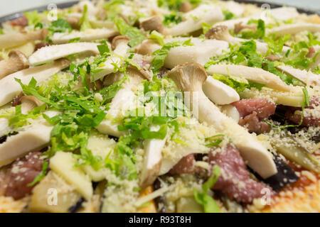 Fresh homemade pizza ready to bake, with King Trumpet mushroom (Pleurotus eryngii), aka French Horn, King Oyster, King Brown mushroom; celery, bacon - Stock Photo
