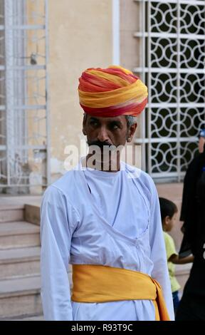 An Indian man in white with orange and yellow turban - Stock Photo