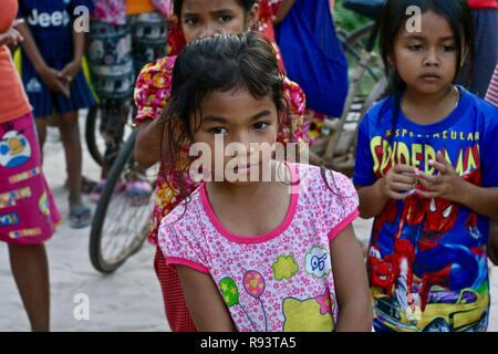A beautiful little Cambodian girl in a schoolyard of a remote village - Stock Photo