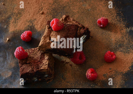 Brownie dessert with raspberries and nuts on dark background - Stock Photo