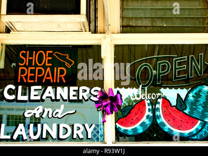 A painted window advertises shoe repair, dry cleaning, laundry services in Water Valley, Mississippi. - Stock Photo