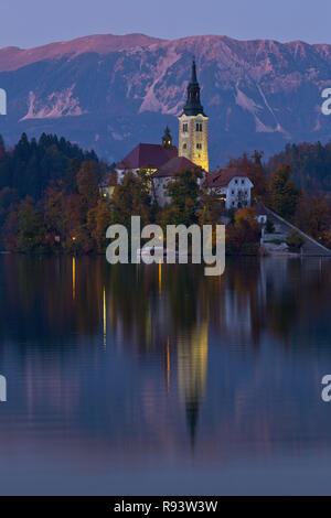 The Church of Assumption on Lake Bled in Slovenia during the blue hour. Fall. - Stock Photo