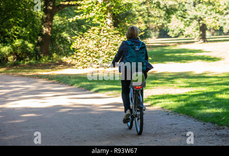 Healthy lifestyle. Woman is riding a bicycle in a path of Tiergarten park, Berlin, Germany. Nature background. - Stock Photo