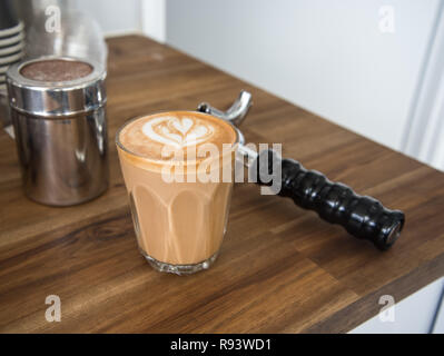 Coffee latte art on a bench with coffee machine tools around it. Cafe latte with a heart on it, beautiful warm drink - Stock Photo