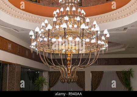 Huge chandelier in the hall. Chandelier on decoarted ceiling of a ballroom. - Stock Photo