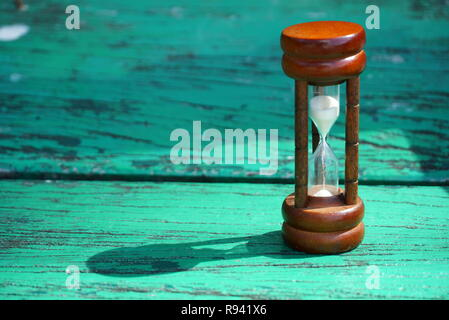 Hourglass on wood table - Stock Photo