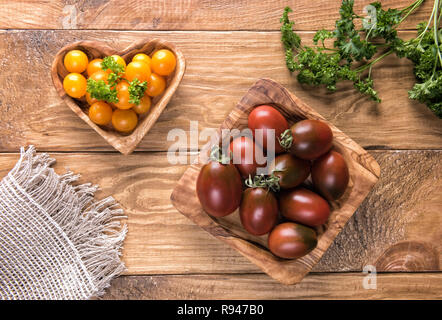 Dark red or black and yellow cherry tomatoes in natural wooden olive tree bowls on textured wooden table surface with green parsley leaves and burlap  - Stock Photo