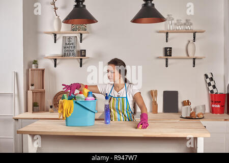 Beautiful cheerful brunette woman in gloves cleaning modern kitchen. Emotional Housekeeper. Bowl full of bottles with disinfectant on table - Stock Photo