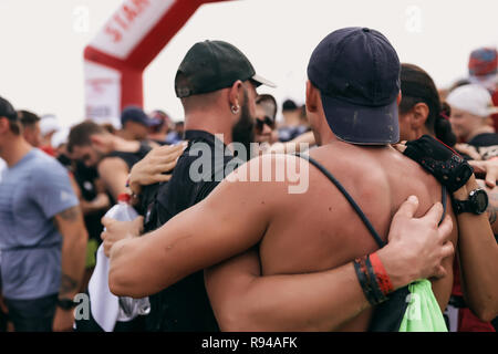 Sport competition outdoors. Group of friends hugging together. Strong men with big muscles, wear caps on the head,accessories on arm.Crowd of people - Stock Photo