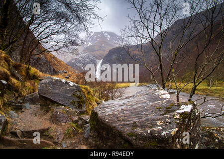 Distant view of Steal Falls looking along Water of Nevis River with lichen covered rocks in the foreground - Stock Photo
