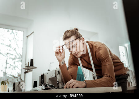 Handsome long-haired fashion dressmaker in eyeglasses looking focused - Stock Photo