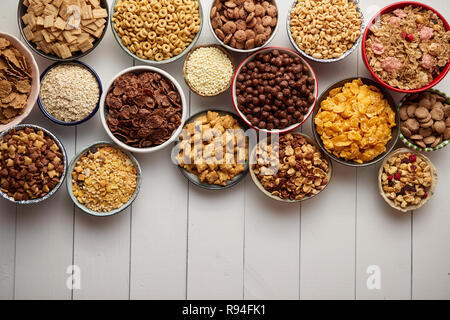 Assortment of different kinds cereals placed in ceramic bowls on table - Stock Photo