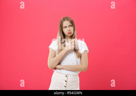 portrait of attractive young girl with sad and disappointed expression, pointing index fingers in both sides, isolated over pink background. Woman confused, don't know what to do. - Stock Photo