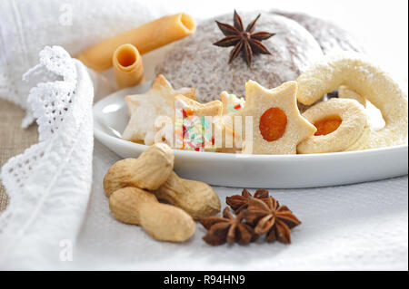 Sweet christmas biscuits and gingerbread on white porcellan, decorated - Stock Photo