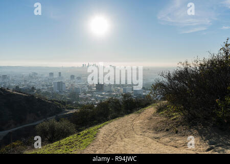 Los Angeles Runyon Canyon Park hiking trail with morning sun, downtown and Hollywood in background. - Stock Photo