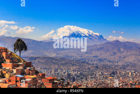 view to the snow cap of Illimani peak and valley full of living houses, El Alto, La Paz city, Bolivia - Stock Photo
