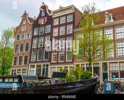 Traditional canal side houses and barge in the capital city of Amsterdam, Holland, Netherlands - Stock Photo
